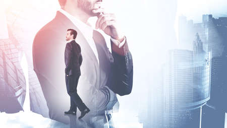 Young businessman walking in blurry abstract city with double exposure of thoughtful businessman. Toned image Banco de Imagens