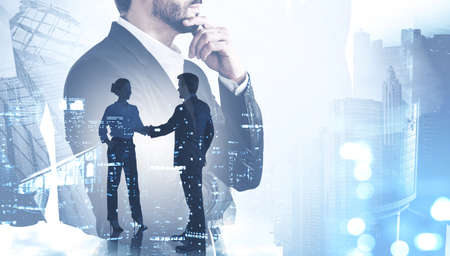 Side view of thoughtful young businessman working in blurry abstract city. Toned image double exposure of man and woman shaking hands
