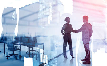 Silhouettes of businessman and businesswoman shaking hands in blurry modern office with double exposure of cityscape. Toned image 免版税图像