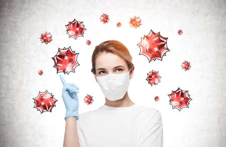 Young woman in protective mask standing near concrete wall with coronavirus around her 免版税图像 - 153315763