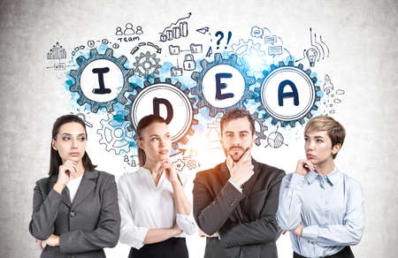 Successful young business team members standing near concrete wall with creative business idea sketch drawn on it 免版税图像 - 153371627