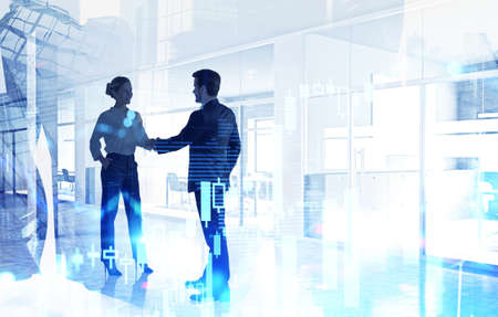 Silhouettes of businessman and businesswoman shaking hands in blurry office with double exposure of financial charts. Toned image 免版税图像 - 153371743