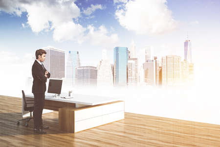 Young businessman standing in panoramic CEO office with concrete floor, table and cityscape. Toned image double exposure