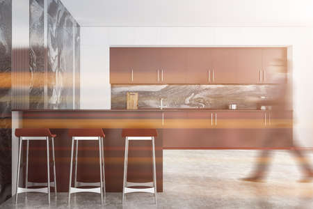 Blurry young man walking in modern kitchen with white and marble walls, brown cupboards and bar with stools. Toned image