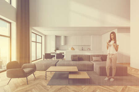 Young woman standing in modern living room with white walls, wooden floor, gray sofa and armchair and kitchen in background. Toned image double exposure