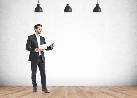 Portrait of bearded young European businessman using tablet computer in concrete room. Concept of technology. Mock up