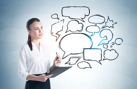 Young businesswoman with notebook standing near gray wall with speech bubbles drawn on it. Concept of communication