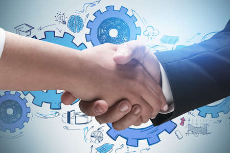 Close up of man and woman shaking hands near gray wall with gears sketch drawn on it. Concept of brainstorming and teamwork