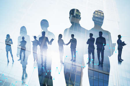 Silhouettes of business people in blurry city with double exposure of digital charts. Toned image