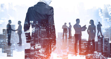 Silhouettes of successful business people working together in blurry city. Concept of teamwork. Toned image Stock Photo