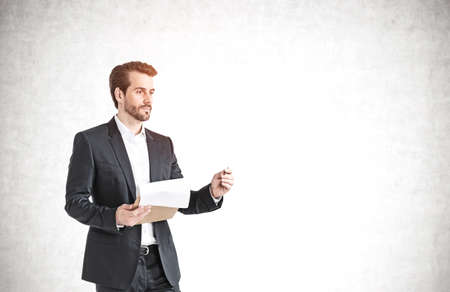 Portrait of bearded young European businessman using tablet computer near concrete wall. Concept of technology. Mock up Stock Photo