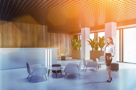Businesswoman talking on smartphone in office waiting room with wooden walls and armchairs. Toned image
