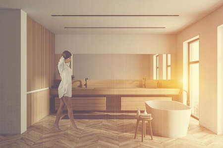 Young woman walking in spacious bathroom with white and wooden walls, comfortable bathtub and double sink. Toned image double exposure