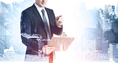 Unrecognizable businessman standing with clipboard in modern city. Concept of paperwork. Toned image double exposure Archivio Fotografico