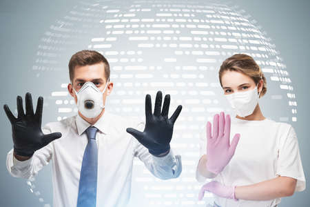 Young businessman and businesswoman wearing protective masks and gloves over concrete background with planet hologram. Toned image double exposure