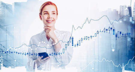 Cheerful young businesswoman using smartphone in blurry abstract city with double exposure of financial graphs. Toned image