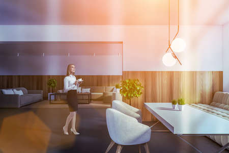 Young woman walking in modern dining room with white and wooden walls, tiled floor and long table with white armchairs. Toned image