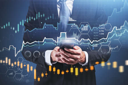 Front view of businessman using smartphone over blurry blue background with double exposure of financial graph. Toned image