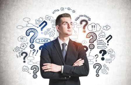 Portrait of confident young businessman standing with crossed arms near concrete wall with question marks drawn on it