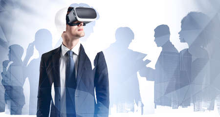 Portrait of young European businessman in VR glasses standing in blurry abstract city with his teammates in background. Concept of hi tech and virtual reality. Toned image double exposure