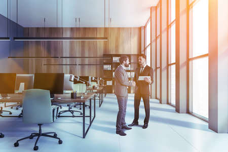 Portrait of two businessmen talking in modern open space office with gray and wooden walls, concrete floor and rows of computer tables. Toned image
