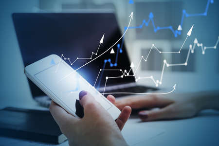 Hands of businesswoman using smartphone and laptop in blurry office with double exposure of financial graphs. Toned image