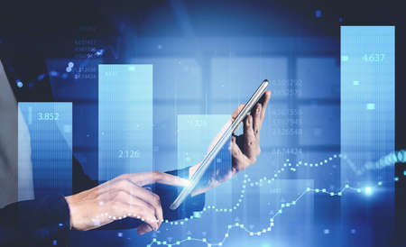 Side view of businesswoman using tablet computer in blurry office with double exposure of financial graph. Toned image Standard-Bild