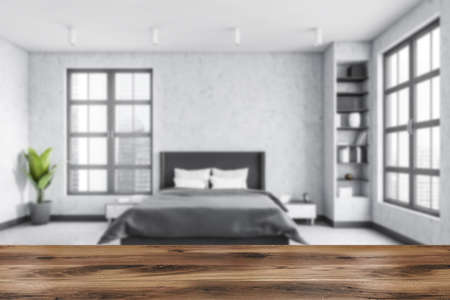 Gray living room blurred with wooden desk on foreground with marble floor, bed and gray linens. Light gray minimalist bedroom with shelves and books. Windows with city view, 3D rendering