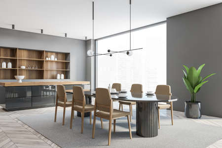 Gray wooden dining room with light gray parquet floor and gray wall, side view. Oval table with dishes and six chairs near big window, counter desk and plant, 3D rendering no people