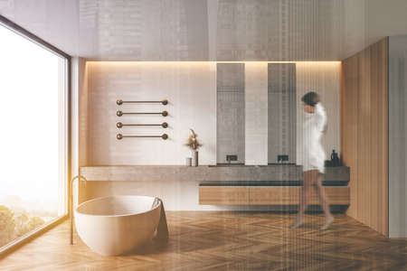 Blurry young woman walking in modern bathroom with white and wooden walls, wooden floor, comfortable bathtub and double sink. Toned image double exposure