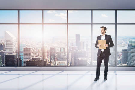 Portrait of young businessman with clipboard standing in empty panoramic office. Concept of paperwork and leadership. Toned image Reklamní fotografie