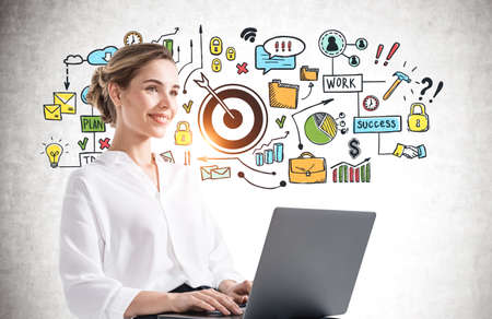 Portrait of smiling young woman using laptop near concrete wall with business goal sketch drawn on it.