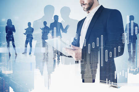 Bearded young businessman using tablet in blurry night city with his team and double exposure of financial graphs. Toned image