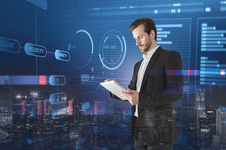 Bearded young businessman using tablet in blurry night city with double exposure of financial interface. Toned image