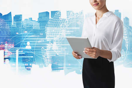 Unrecognizable businesswoman working with tablet in blurry night city with double exposure of social network interface. Concept of recruitment. Toned image