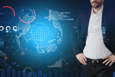 Unrecognizable young businessman standing in blurry night city with double exposure of planet hologram and graphs. Toned image. Elements of this image furnished by NASA