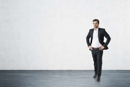 Full length portrait of confident young European businessman standing in concrete wall room. Concept of success. Mock up