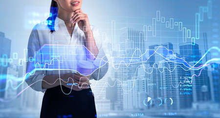 Portgrait of attractive young business woman in white shirt holding coffee cup and pondering about behavior of financial market. Forex graph background. double exposure. Trading and analytics.