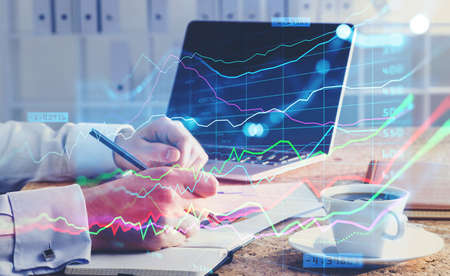 A financial analyst is making notes and trying to settle a new approach to boost the business and achieve exceptional financial results. Laptop on background. Double exposure. Banque d'images