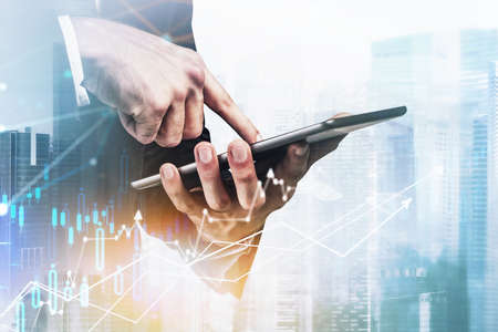 Businessman wearing formal suit is touching the tablet screen. Singapore city skyscraper view in the background. Forex candlestick, chart and graph in the foreground. Concept of successful trading