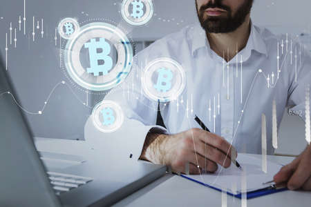 Businessman wearing formal suit is looking at laptop and putting down notes, analyzing and predict the behavior of cryptocurrency market. Forex candlestick, bitcoin logotype, office background
