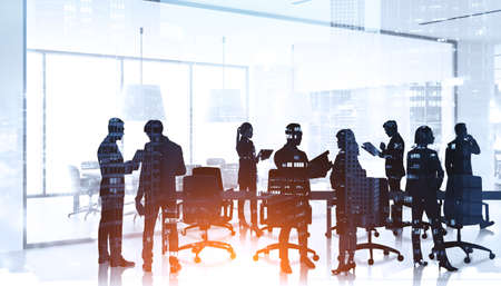 Silhouettes of diverse business people in meeting room, teamwork in a big company. Office interior and buildings at night, double exposure. Concept of modern office with managers, partners Stockfoto