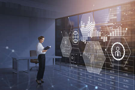 Businesswoman wearing white shirt is standing at office making notes in a book in front of digital interface with hologram of globe, candlestick, bar diagram. Concept of analyzing electronic data