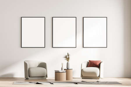 Modern living room interior with two armchairs and small table. Three mock up framed posters on white wall. Reading and relax concept. No people. 3d rendering.