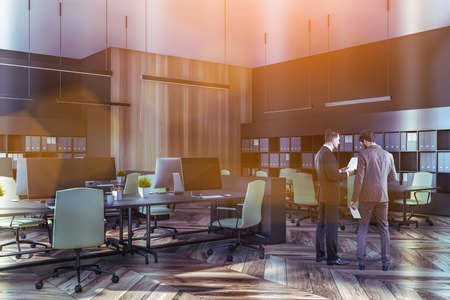 Portrait of two young businessmen working together in modern office. Concept of leadership and corporate life. Toned image