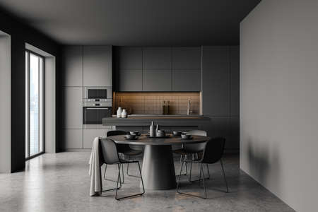 Interior of stylish kitchen with gray walls, concrete floor, comfortable round dining table with four chairs, bar and cupboards. Blurry cityscape window. 3d rendering