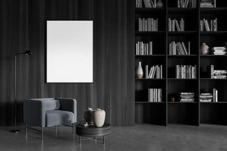 Wooden gray art interior with bookshelf and books with vases. One blank copy space frame above armchair with lamp, reading room in library with concrete floor, 3D rendering Imagens