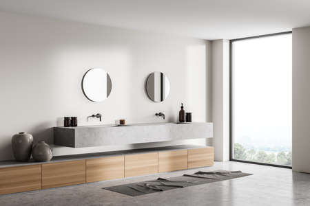 Light bathroom with concrete sinks, round mirrors, art decoration and concrete floor. Modern stylish bathing room interior with window on countryside, 3D rendering