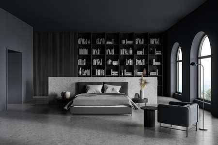 Gray bedroom interior with bed and linens on concrete floor, big bookshelf with books and decoration, armchair with lamp and coffee table. Art bedroom with windows, 3D rendering no people