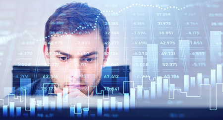 Portrait of trader businessman who is carrying out a research on desktop computer. Forex graph background with overlay. Concept of trading and analytics.